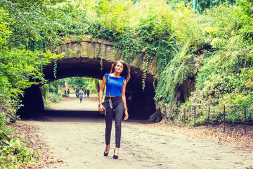 Young American Woman traveling in New York, wearing blue sleeveless shirt, black pants, shoes, carrying shoulder bag, walking at Central Park, relaxing. Street bridge with green leaves on background..