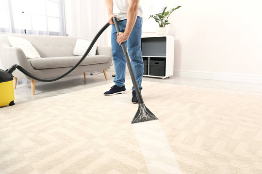 Man removing dirt from carpet with vacuum cleaner in room