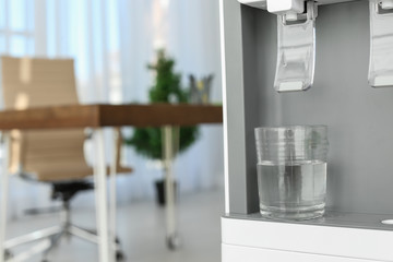 Modern water cooler with glass in office, closeup. Space for text