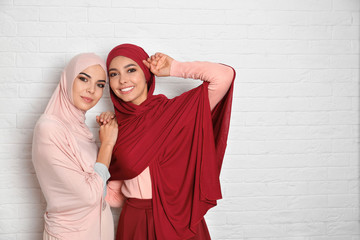 Portrait of young Muslim women in hijabs against brick wall. Space for text