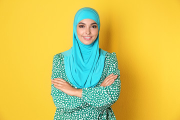 Portrait of young Muslim woman in hijab against color background