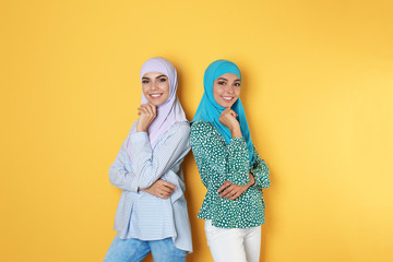 Portrait of young Muslim women in hijabs against color background