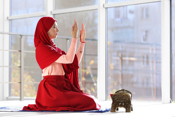 Muslim woman in hijab praying on mat indoors. Space for text