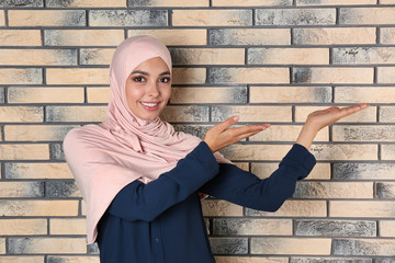 Portrait of young Muslim woman in hijab against brick wall