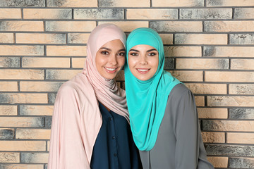 Portrait of young Muslim women in hijabs against brick wall
