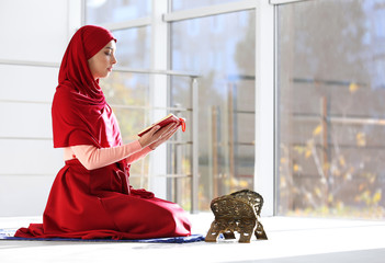Muslim woman in hijab reading Koran indoors. Space for text