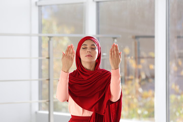 Young Muslim woman in hijab praying indoors