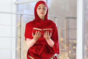 Muslim woman in hijab reading Koran indoors