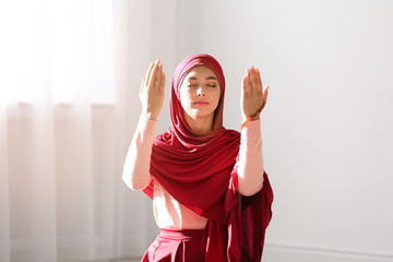 Young Muslim woman in hijab praying indoors