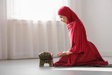 Muslim woman in hijab praying on mat indoors
