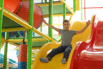 Cute little child playing at indoor amusement park