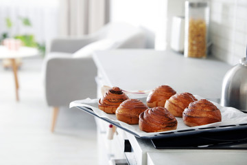 Tray with freshly oven baked buns on stove in kitchen. Space for text