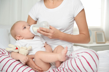 Lovely mother holding and feeding her baby from bottle on bed at home