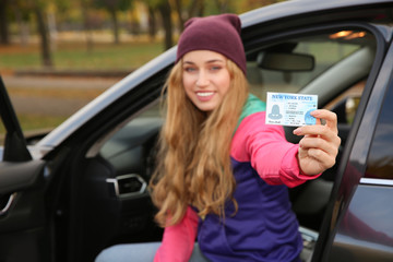 Happy woman holding driving license in car. Space for text
