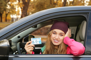 Happy woman holding driving license in car