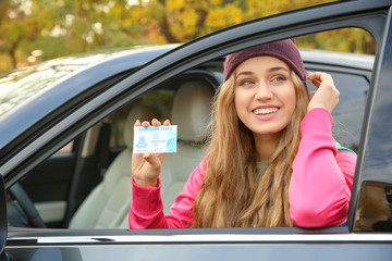 Young woman holding driving license near open car