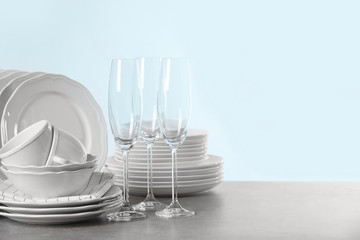 Set of clean dishes on table against light background. Space for text