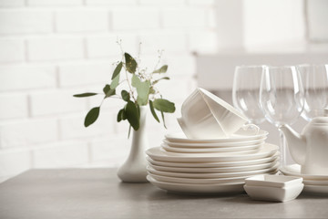 Set of clean dishes on table against blurred background. Space for text