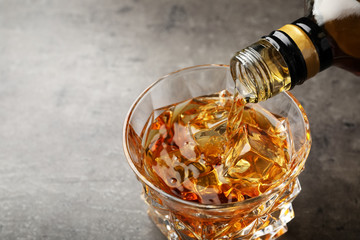 Pouring whiskey from bottle into glass with ice cubes on table. Space for text