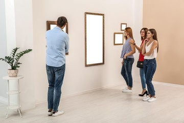 People viewing exposition in modern art gallery