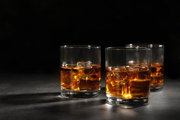 Golden whiskey in glasses with ice cubes on table. Space for text