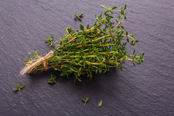 essential oil of thyme on a dark stone background