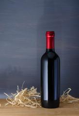 botella de vino tinto tapa roja en fondo azul y mesa de madera