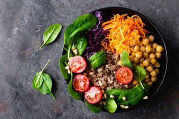 Photo Stands Ready meals Healthy vegetarian dish with buckwheat and vegetable salad of chickpea, kale, carrot, fresh tomatoes, spinach leaves and pine nuts. Buddha bowl. Balanced food. Delicious detox diet.Top view