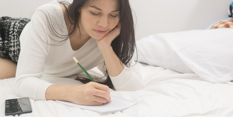 Young asian woman is writing in notebook while sitting in the bed.
