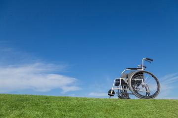 青空バックを背景に芝の上に置かれた無人の車イス。福祉、介護、病気、障害者、老後イメージ