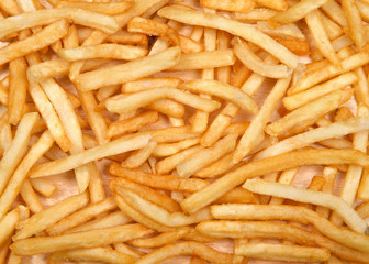 Top view flat lay of many french fries on a light wood table. French fries have been popularized worldwide in large part by the large American fast food chains.