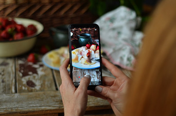 A woman taking a picture by phone with dumplings with strawberries