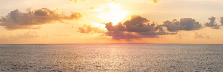 Panoramic beautiful view on sunset over the ocean. Сolorful cloudy sky and setting sun