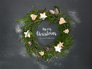 christmas wreath on black background with many different christmas items and lettering merry christmas