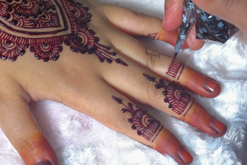 Image detail of henna being applied to hand over white fabric. Selective focus.
