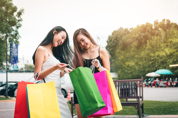 Two asian women standing at outlet mall and looking inside shopping bags paper.