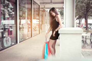 Asian teenage girls standing at poles and holding shopping bags.