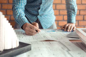 Hand of young engineering man drawing on blueprint with model on desk.