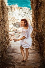 Young woman walking down a narrow rocky staircase
