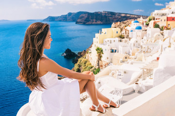 Wall Mural - Europe summer travel destination Santorini tourist woman on vacation relaxing. Asian girl in white dress looking at famous white village Oia with the mediterranean sea and blue domes.