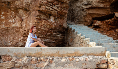Young woman in beach dress sitting next to stairs in front of rocky background