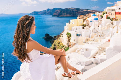 Wall mural Europe summer travel destination Santorini tourist woman on vacation relaxing. Asian girl in white dress looking at famous white village Oia with the mediterranean sea and blue domes.