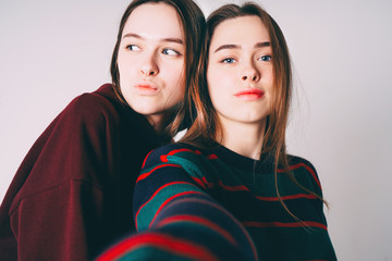 Two sisters twins beautiful girls in casual taking selfie on fro