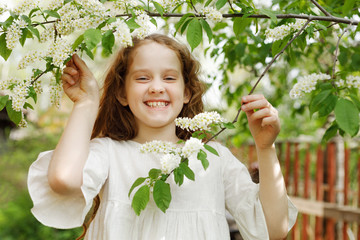 Little girl with a branch blooming tree.