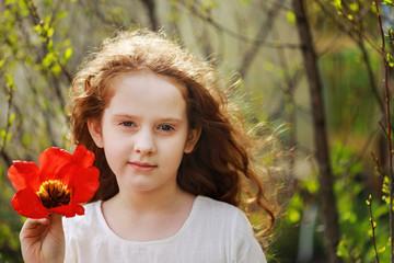 Little girl with tulip flower, summer background.