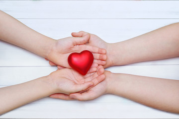 Children hand with red heart.
