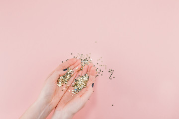 Woman hands covered golden stars confetti on pink