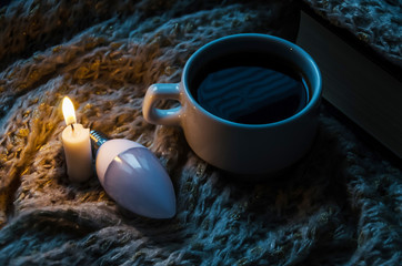 a cup of coffee, a light bulb, a candle lit in the dark