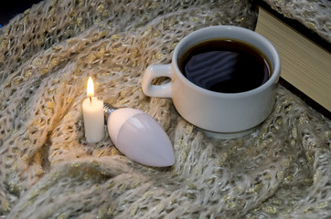 a cup of coffee, a light bulb, a candle