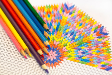 drawing mandala with colored pencils on a drawing template.